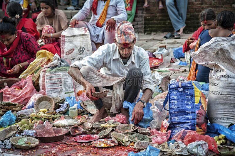 Unidentified Nepalese Newari man selling vegetables and flowers in  Bhaktapur, listed as a World Heritage by UNESCO stock photo