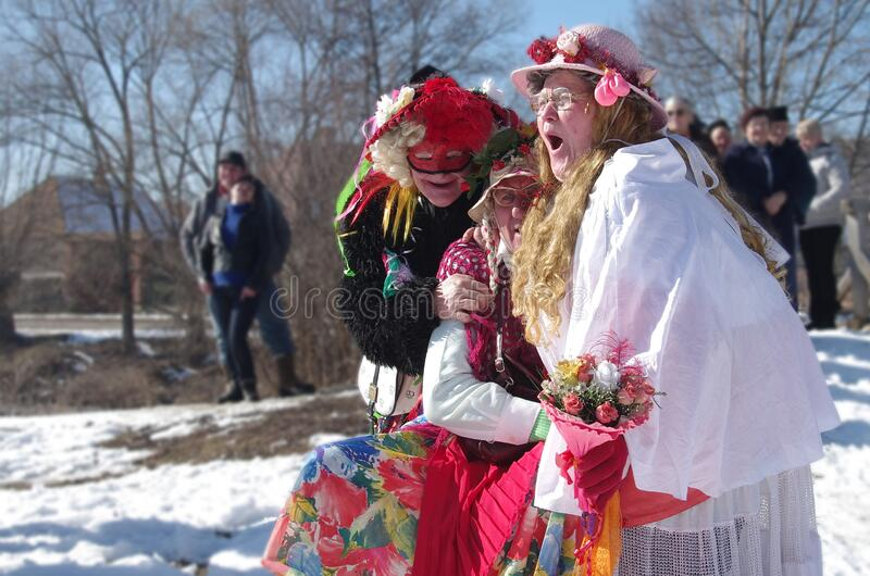 Funny moment at the carnival. Unidentified old man and two old woman are joking the at winter ending carnival
