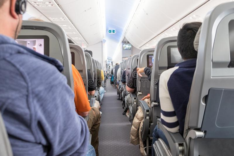 Unidentified passengers sitting on seats in airplane stock photos
