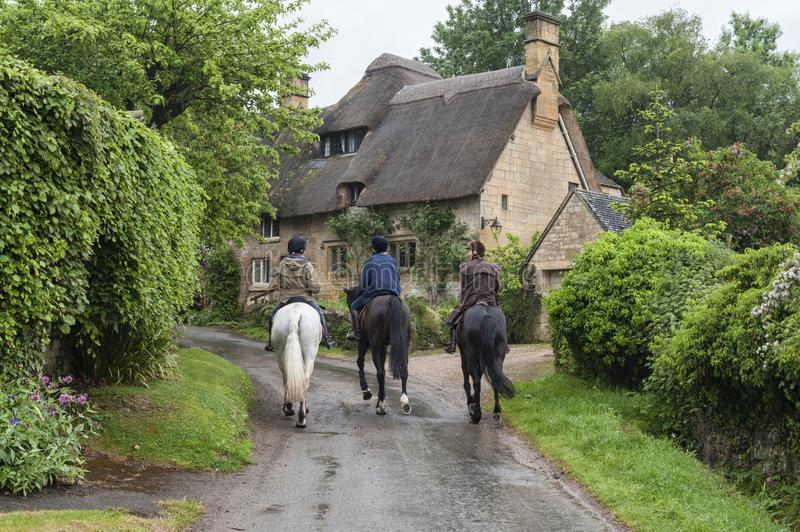 Unidentified people and horses near cottages in the village of Stanton, Cotswolds district of Gloucestershire. STANTON, ENGLAND - MAY, 26 2018:  Unidentified royalty free stock photos