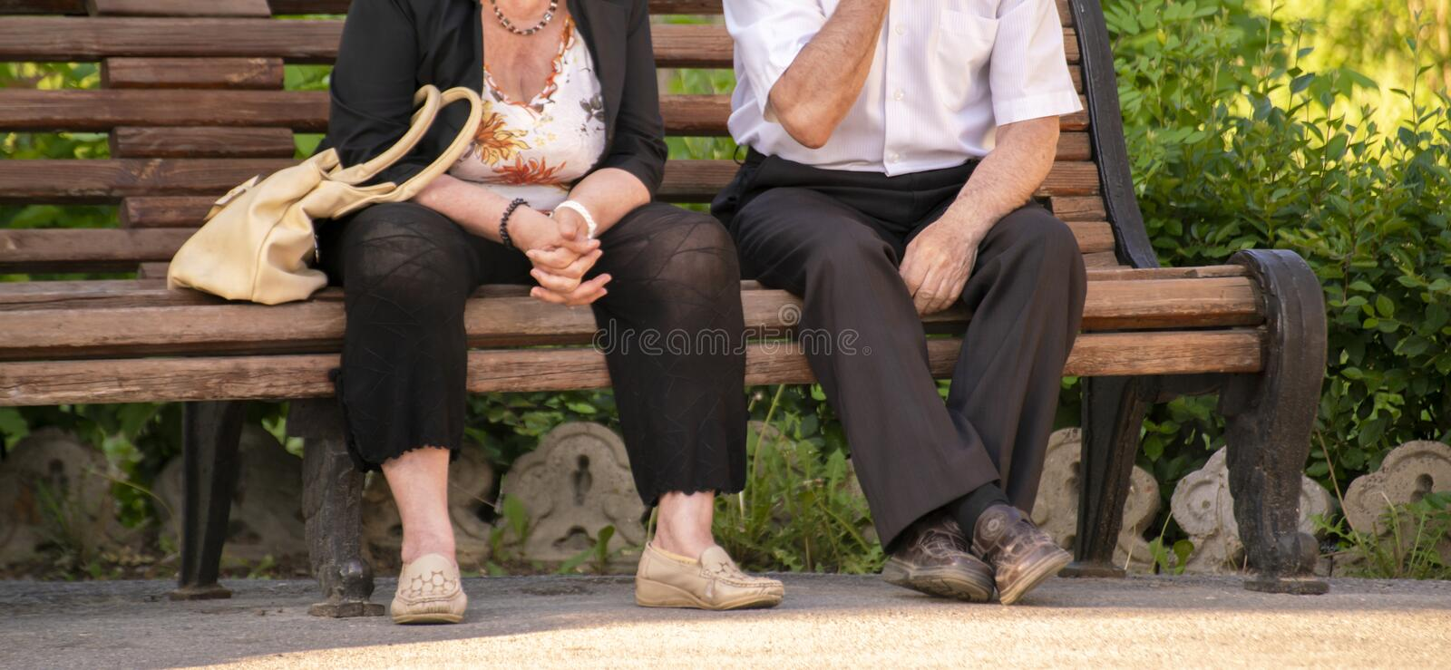 Unidentified people sit on a wooden bench in the green park, chatting in a public places. Unidentified people sit on a wooden bench in the green park, chatting royalty free stock photo