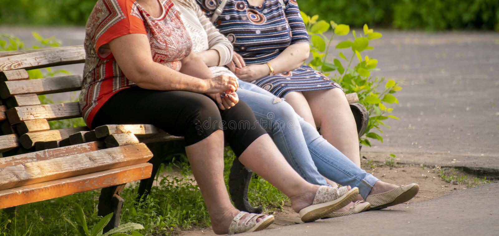 Unidentified people sit on a wooden bench in the green park, chatting in a public places. Unidentified people sit on a wooden bench in the green park, chatting stock photo