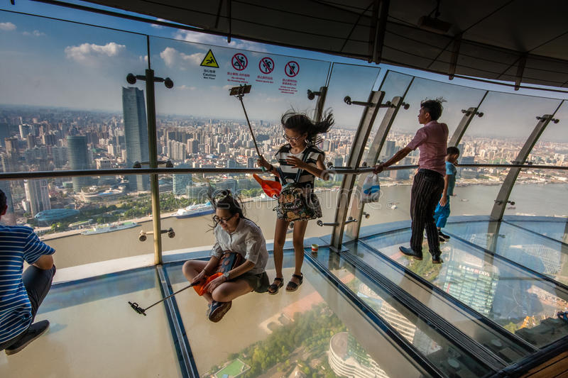An unidentified people take selfie photo on transparent glass floor. SHANGHAI, CHINA - AUGUST 29, 2016: An unidentified people take selfie photo on transparent stock photos