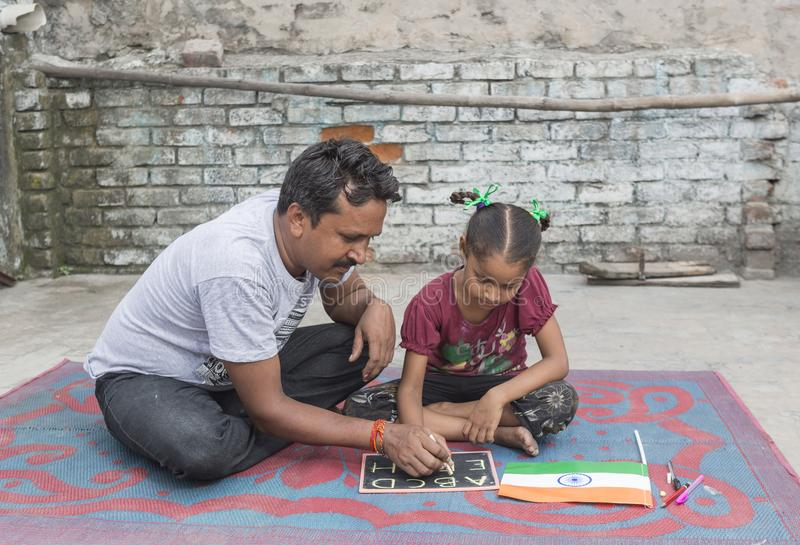 A girl studying elementary education in open school. Unidentified person in ludhiana, punjab, india helping his unidentified daughter in study on 15 august 2017 royalty free stock photos