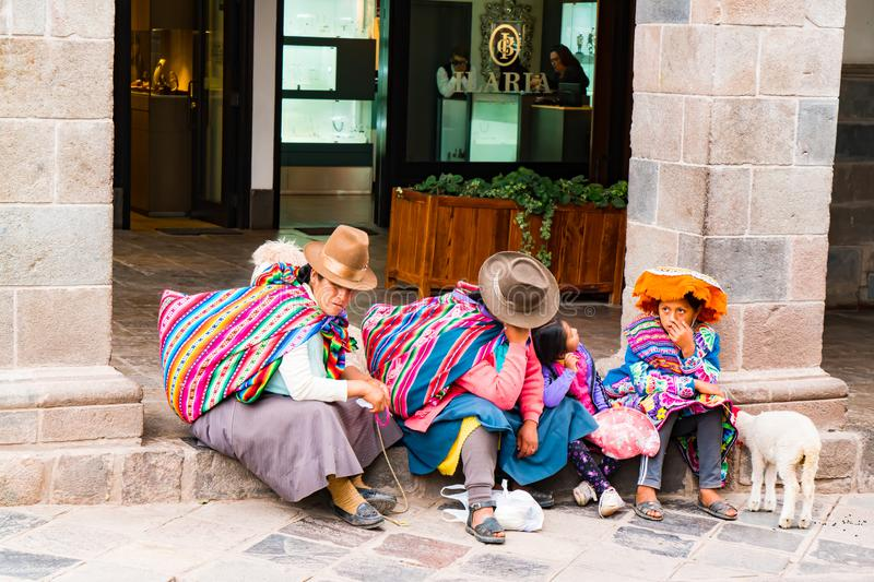 Unidentified Peruvian people with their animal sitting in front of a shop in cusco to take a rest stock image
