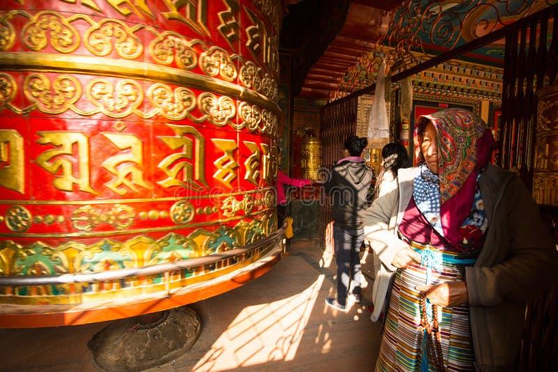 Unidentified pilgrimage near spinning Big Tibetan Buddhist prayer wheel at Boudhanath Stupa stock images