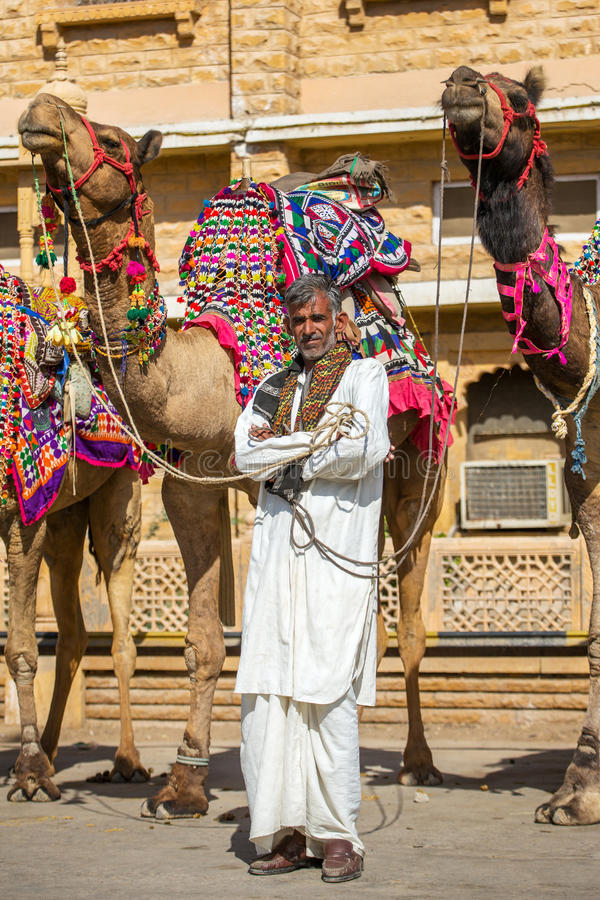 Unidentified rajasthani man with camels. Jaisalmer, India - March 3, 2016: Unidentified rajasthani man with camels waiting for tourists in Jaisalmer, India royalty free stock image