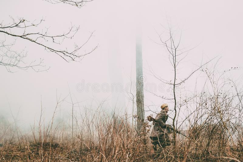Unidentified re-enactor dressed as Soviet russian soldier running through woods stock images