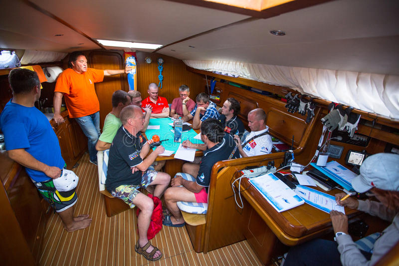 Unidentified sailors on skipper's briefing in the yacht wardroom during sailing regatta among Greek island. HYDRA, GREECE - CIRCA OCT, 2014: Unidentified sailors royalty free stock image