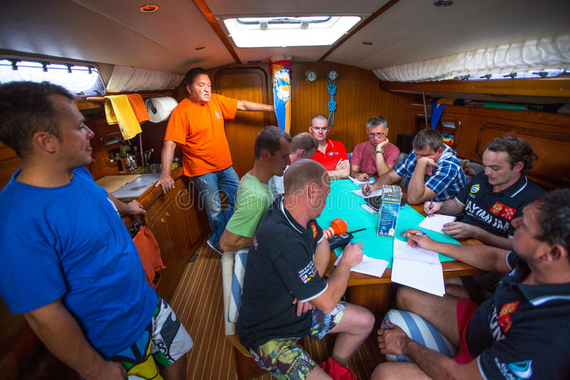 Unidentified sailors on skipper's briefing in the yacht wardroom during sailing regatta 12th Ellada. HYDRA, GREECE - CIRCA OCT, 2014: Unidentified sailors on stock photos