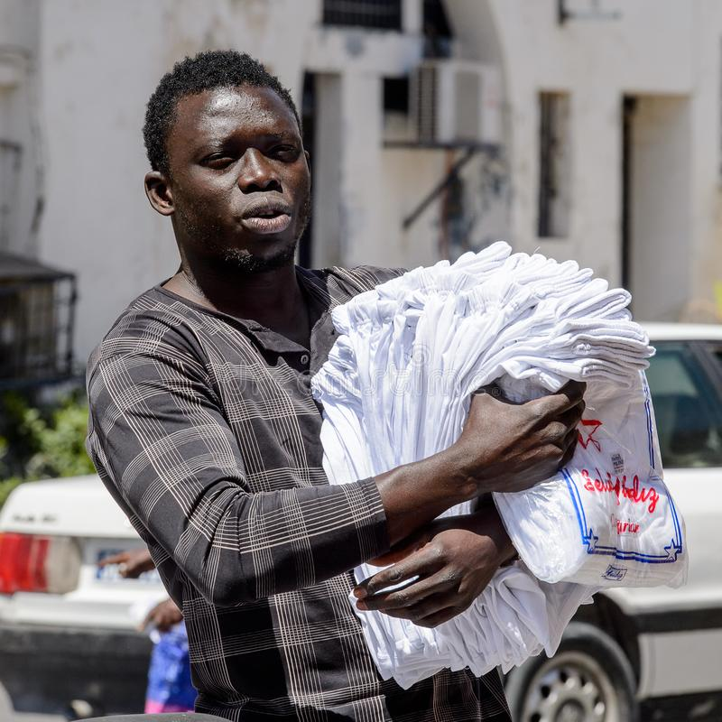 Unidentified Senegalese man walks along the street with goods f stock image