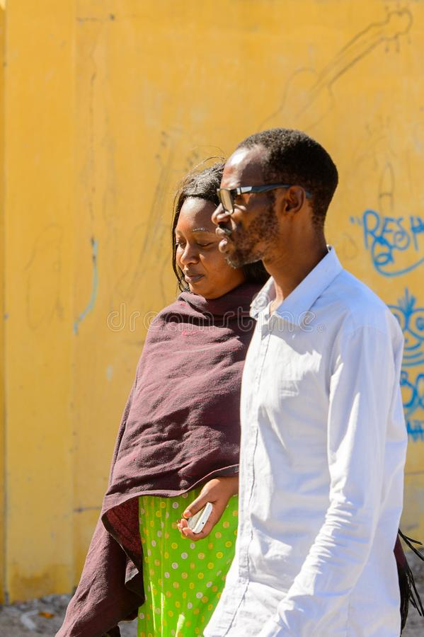 Unidentified Senegalese man and woman walk along the street in. SAINT LOUIS, SENEGAL - APR 24, 2017: Unidentified Senegalese man and woman walk along the street royalty free stock images