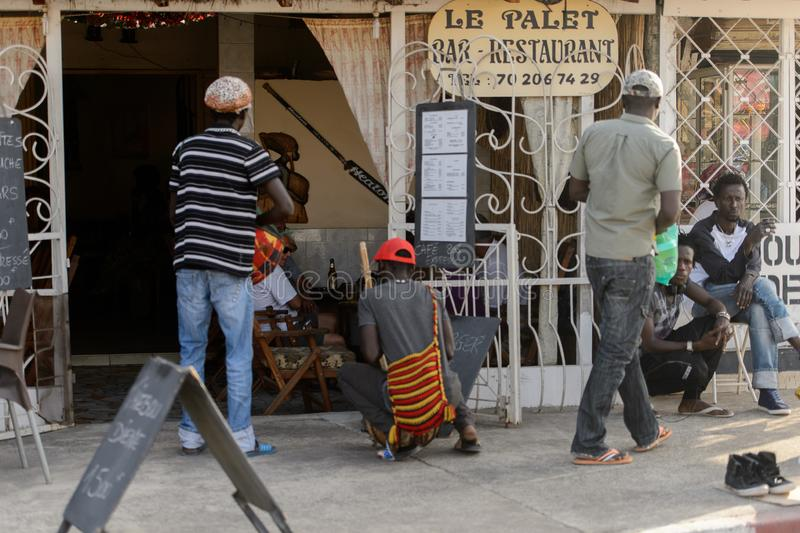 Unidentified Senegalese people stand near the cafe. royalty free stock image