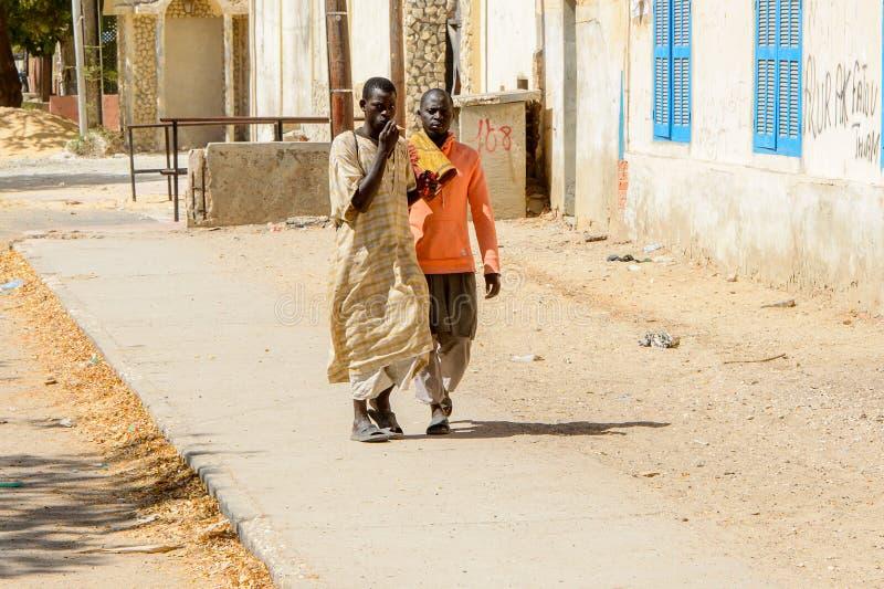 Unidentified Senegalese two men walk along the street in Saint. SAINT LOUIS, SENEGAL - APR 24, 2017: Unidentified Senegalese two men walk along the street in royalty free stock images