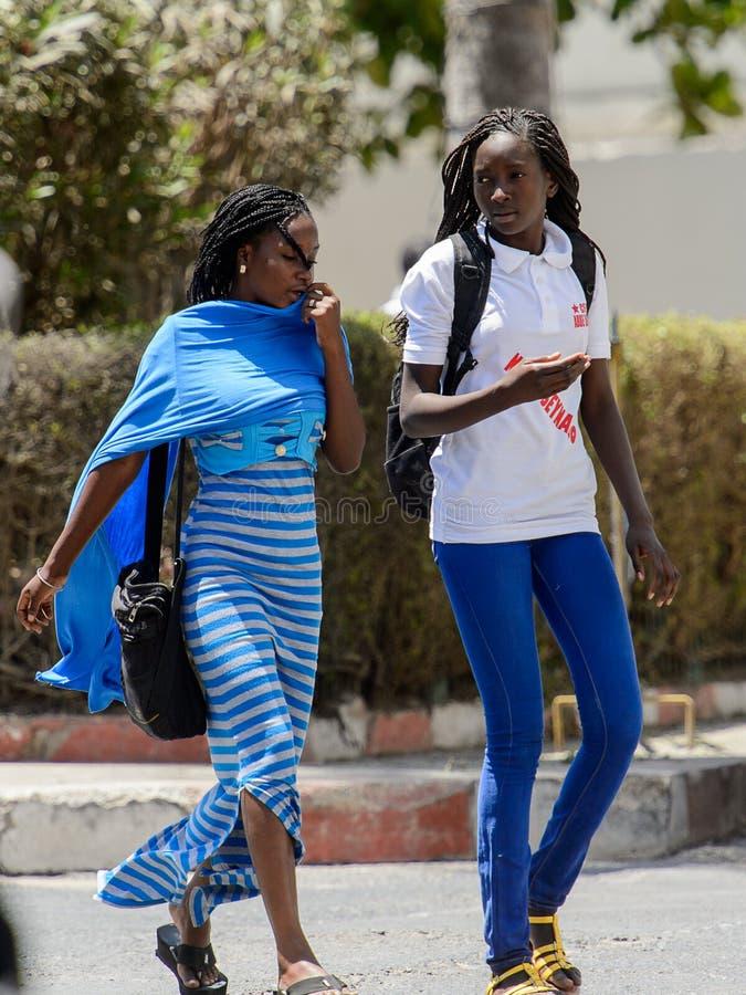 Unidentified Senegalese women walk along the street in the cent. SAINT LOUIS, SENEGAL - APR 24, 2017: Unidentified Senegalese women walk along the street in the royalty free stock photo