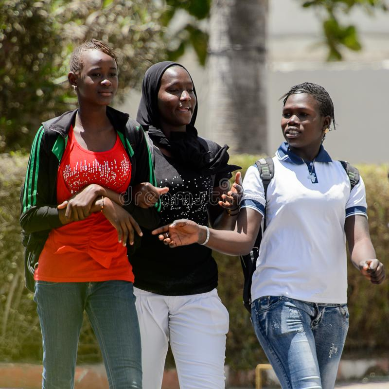 Unidentified Senegalese women walk along the street in the cent. SAINT LOUIS, SENEGAL - APR 24, 2017: Unidentified Senegalese women walk along the street in the royalty free stock photography