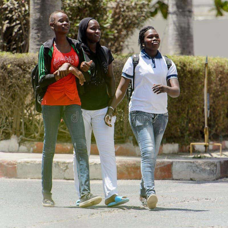 Unidentified Senegalese women walk along the street in the cent. SAINT LOUIS, SENEGAL - APR 24, 2017: Unidentified Senegalese women walk along the street in the royalty free stock photos