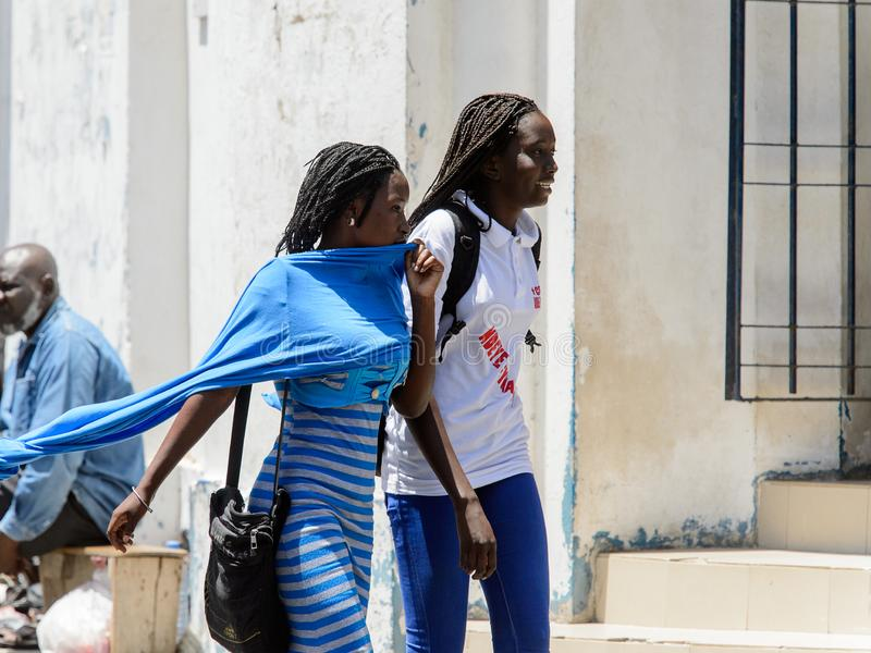 Unidentified Senegalese women walk along the street in the cent. SAINT LOUIS, SENEGAL - APR 24, 2017: Unidentified Senegalese women walk along the street in the stock photography