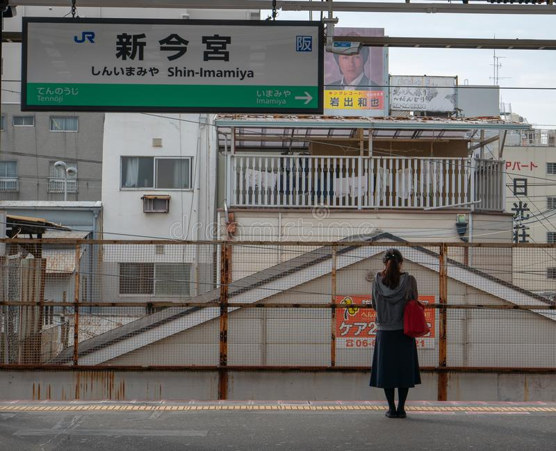 Unidentified single Japansese lady wait for passenger train in Shin-Imamiya station in Osaka, Japan stock images