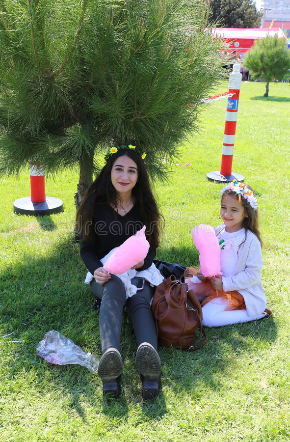 Unidentified Sisters sitting on grass and enjoying their cotton candies royalty free stock photos