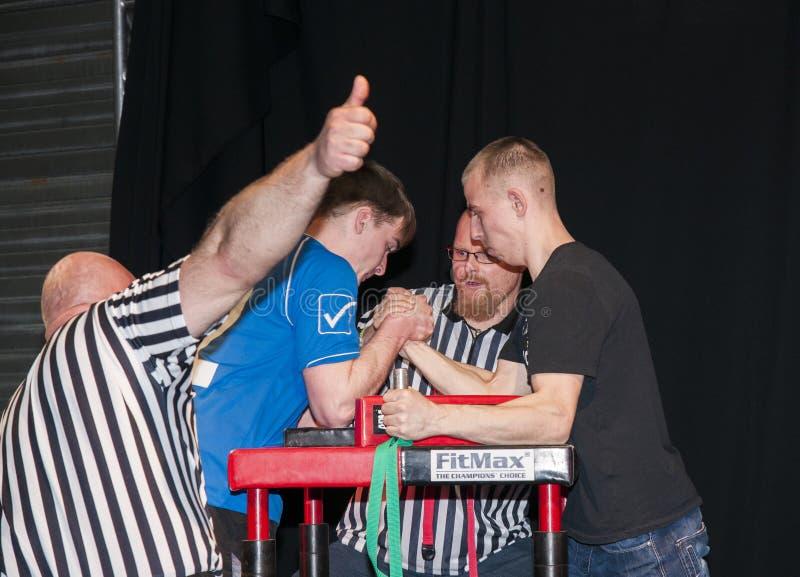 Unidentified sportsmen compete in arm wrestling. Szczecin, Poland - April 12, 2015: Unidentified sportsmen compete in arm wrestling royalty free stock images
