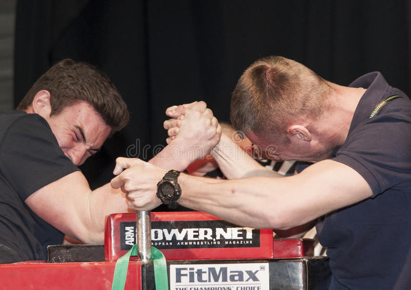 Unidentified sportsmen compete in arm wrestling. Szczecin, Poland - April 12, 2015: Unidentified sportsmen compete in arm wrestling stock image