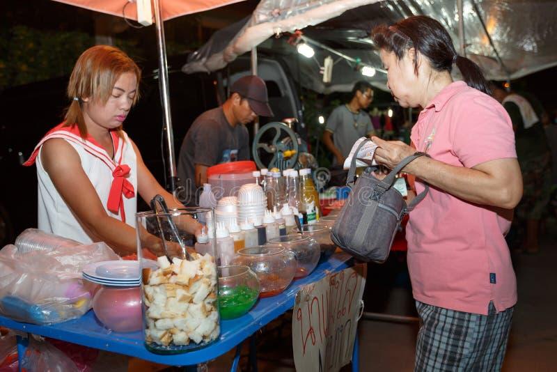 An unidentified Thai people sells food on night market wall street. PHITSANULOK, THAILAND-JUNE 21: An unidentified Thai people sells food on night market walk royalty free stock image