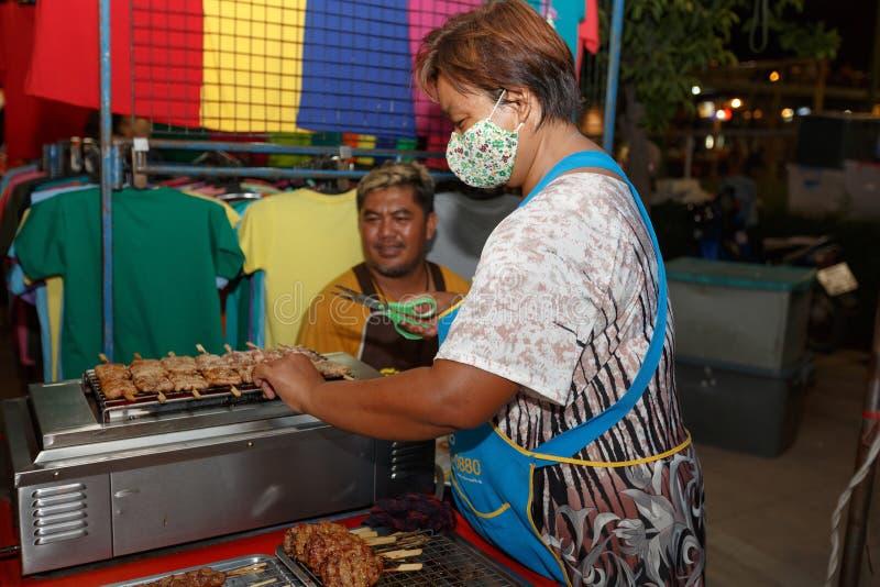 An unidentified Thai people sells roasted pork on night market walk street. PHITSANULOK, THAILAND-JUNE 21: An unidentified Thai people sells roasted pork on stock photography