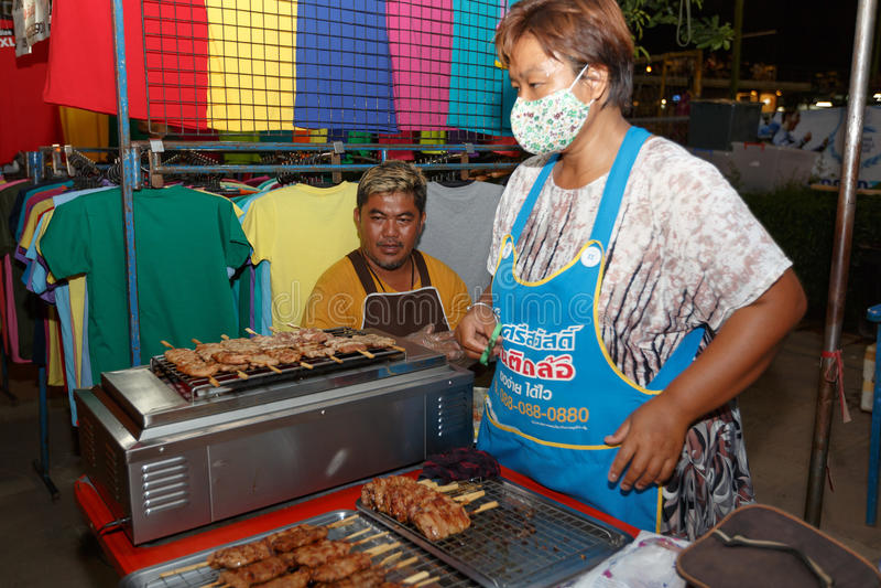 An unidentified Thai people sells roasted pork on night market walk street . PHITSANULOK, THAILAND-JUNE 21: An unidentified Thai people sells roasted pork on royalty free stock images