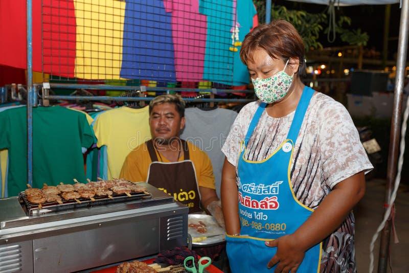 An unidentified Thai people sells roasted pork on night market walk street. PHITSANULOK, THAILAND-JUNE 21: An unidentified Thai people sells roasted pork on royalty free stock image