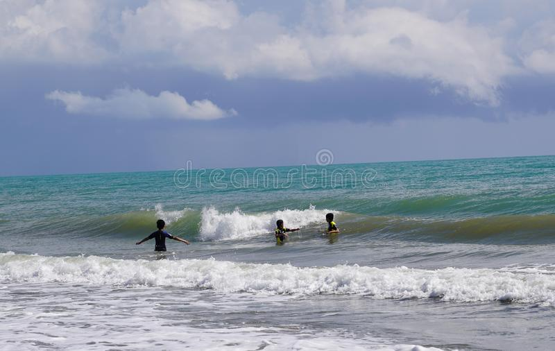 Unidentified three children enjoying wavy Mediterranean stock photo