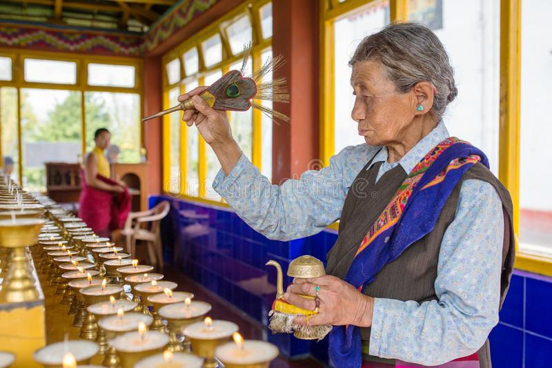 Unidentified tibetan woman praying in Tsuglagkhang buddhist monastery, Gangtok, Sikkim, India. Gangtok, India - May 3, 2017: Unidentified tibetan woman praying stock photo