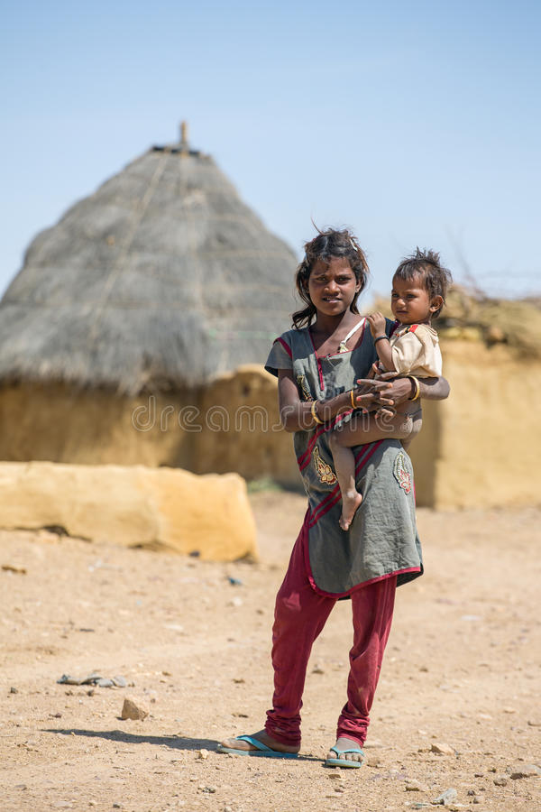 Unidentified tribal girl holding a baby in traditional village royalty free stock images