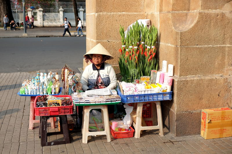 Unidentified woman is selling souvenir stuffs at the corner of Notre Dame Cathedral Basilica, called Nha Tho Duc Ba in Vietnamese. The photo was taken in Saigon stock images