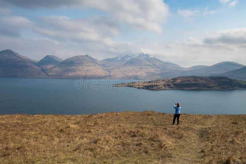 Woman taking a photo of the dramatic scenery of Ben More mountain in Scotland stock photos