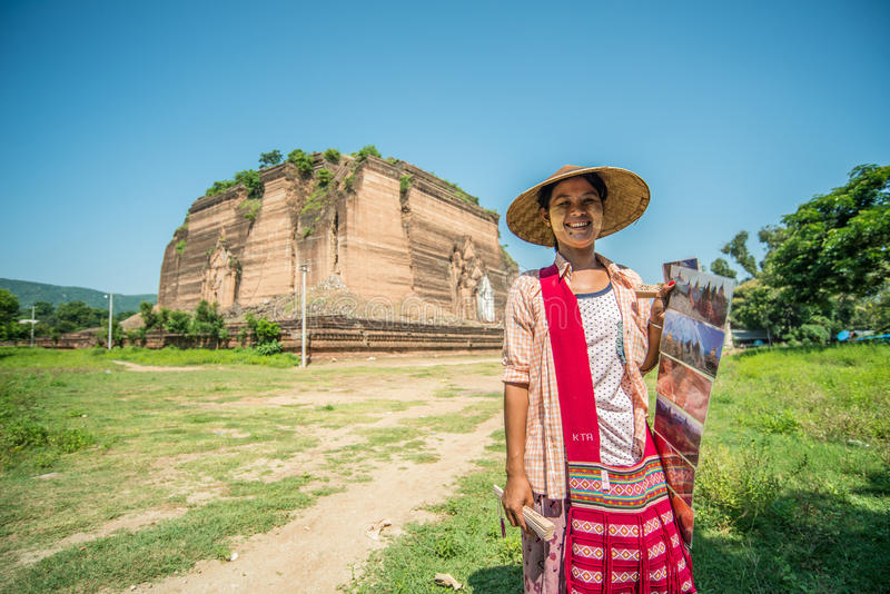 An unidentified women sells postcard in front of Mingun Pa Hto Daw Gyi pagoda Myanmar. Mingun is best known for its gigantic, unfinished stupa, the Mingun stock photos