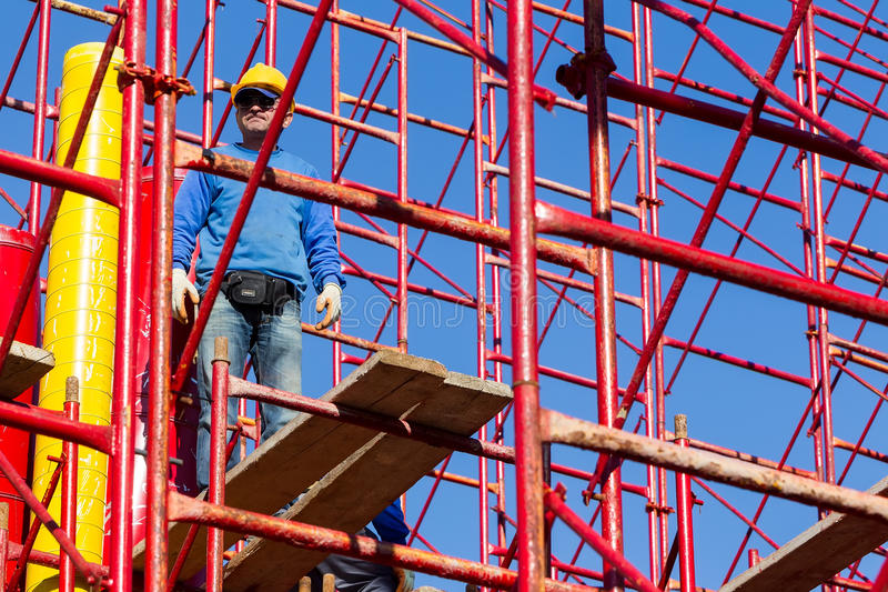 Unidentified workers setting up iron scaffolding at construction royalty free stock photo