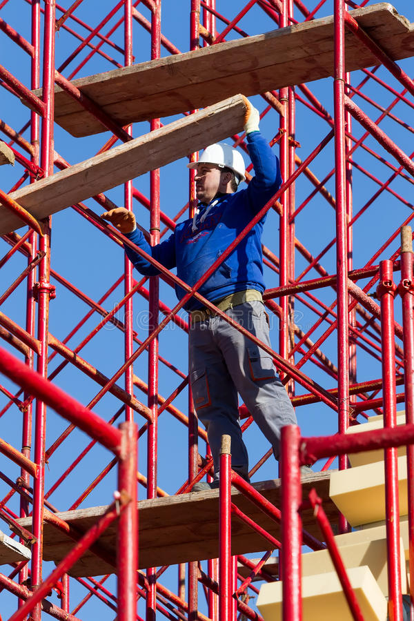 Unidentified workers setting up iron scaffolding at construction stock images