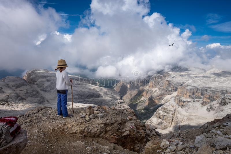 Unidentified young child overlooking the landscape on top of the Sella Group massif. In the Italian Dolomite mountains stock photography