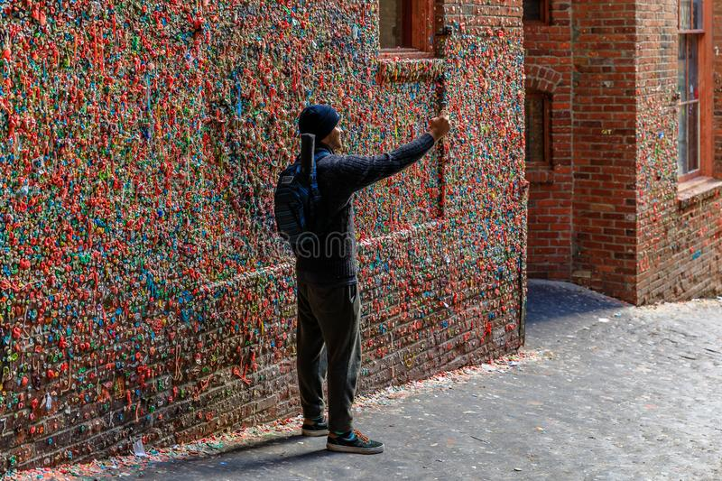 Unidentified young man taking a selfie at the Market Theater Gum Wall in Pike Market royalty free stock photography