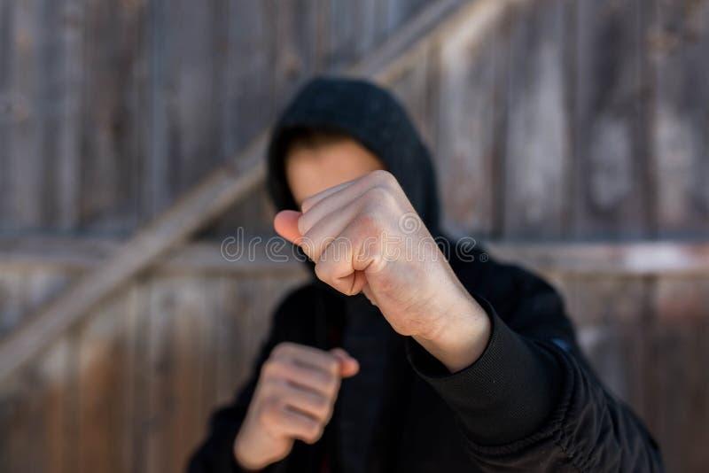 Unidentifizierbarer Teenager, der mit hes bloßen Händen, Fokus auf der Faust angreift lizenzfreie stockfotografie