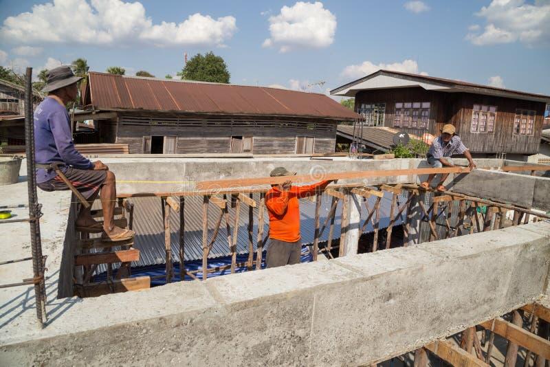 Unidentifliedarbeider die hout installeren tijdens bouw royalty-vrije stock afbeeldingen