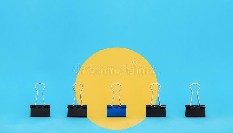 Uniek, leiding, individualiteit, en denk verschillend concept Bureaulevering, de blauwe tribune van de bindmiddelenpaperclip uit  stock fotografie
