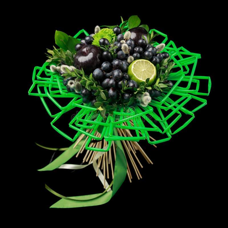 Unieke die gift met de hand gemaakt in de vorm van boeket van bloemen en vruchten met veel groen stro voor dranken op een zwarte  stock foto's