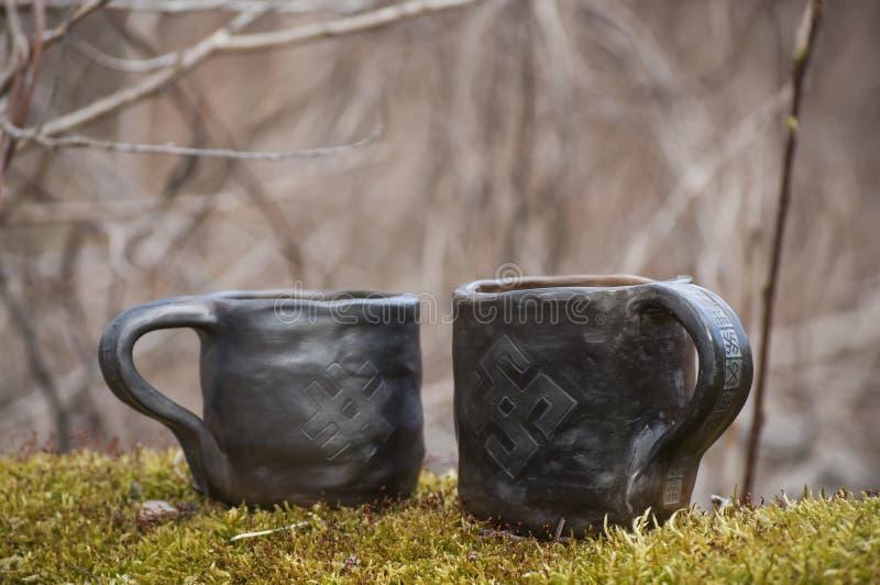 Unieke met de hand gemaakte twee koppen met volkstekens op groen mos met vaag bos op achtergrond royalty-vrije stock foto's