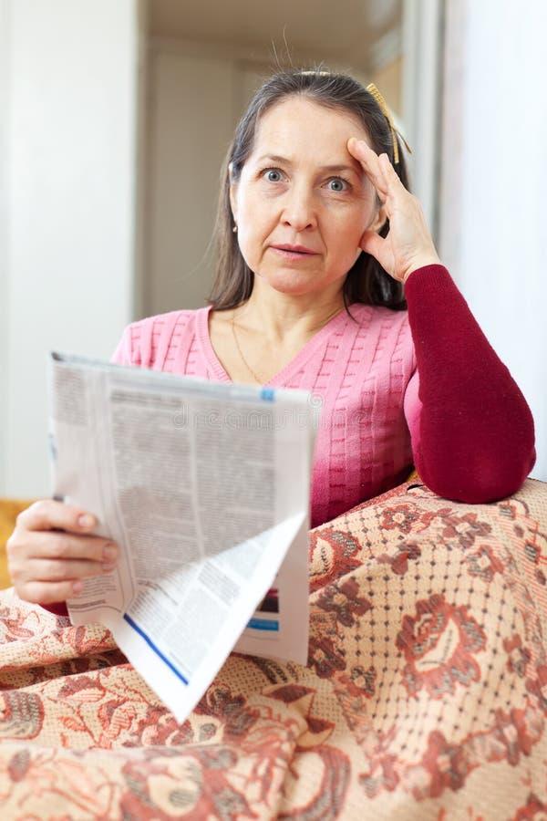 Unieszczęśliwienie dojrzała kobieta z gazetą obraz stock