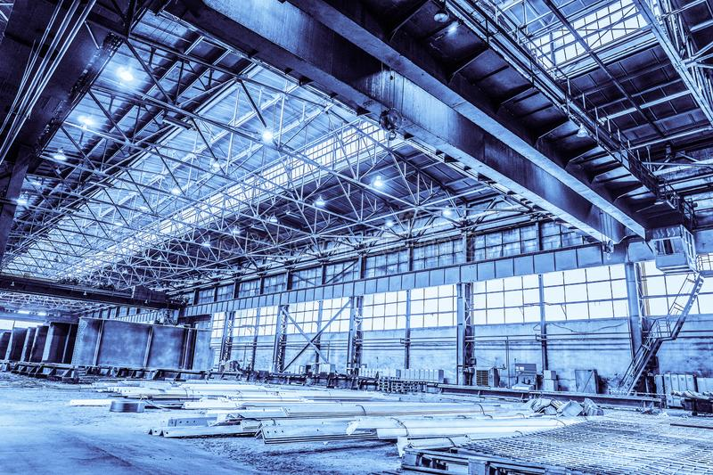 Unified standard typical span prefabricated of a steel frame production building. Industrial metalwork production hall with overhead cranes. Background in blue royalty free stock photos
