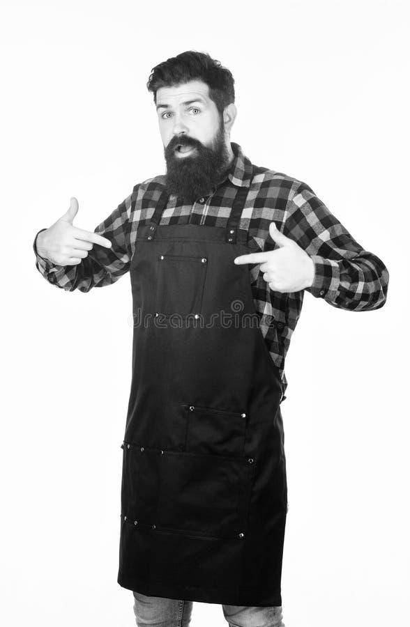 Uniform for barber salon. Barbershop concept. Hairdresser barber salon for men. Man brutal bearded hipster wear apron. Uniform. Barbershop staff. Beard grooming stock photography