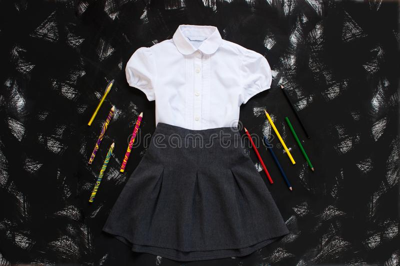 White shirt, grey skirt and stationery supplies on black background. The first of september, new school year royalty free stock images