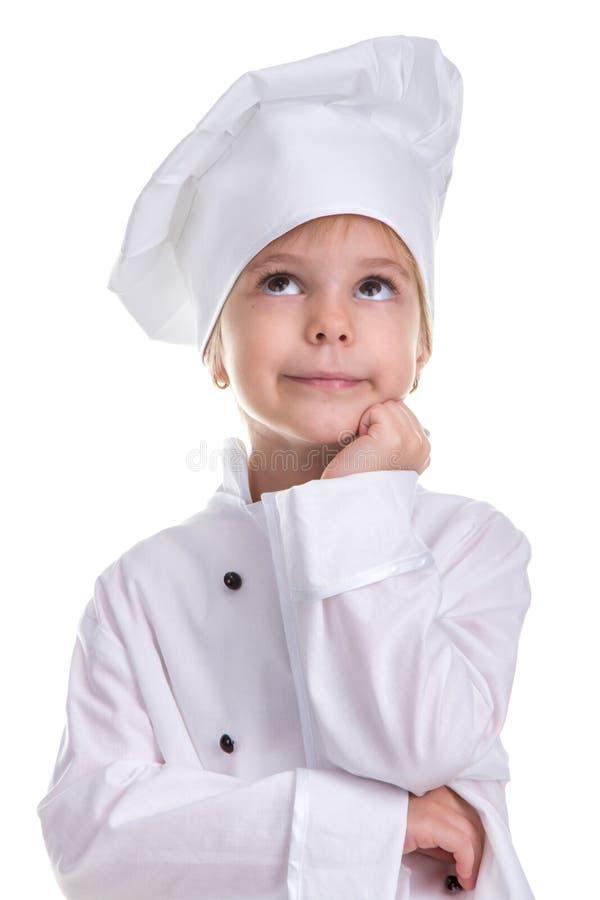 Uniforme branco confundido do cozinheiro chefe da menina isolado no fundo branco, olhando acima, guardando a mão sob o queixo Ret foto de stock